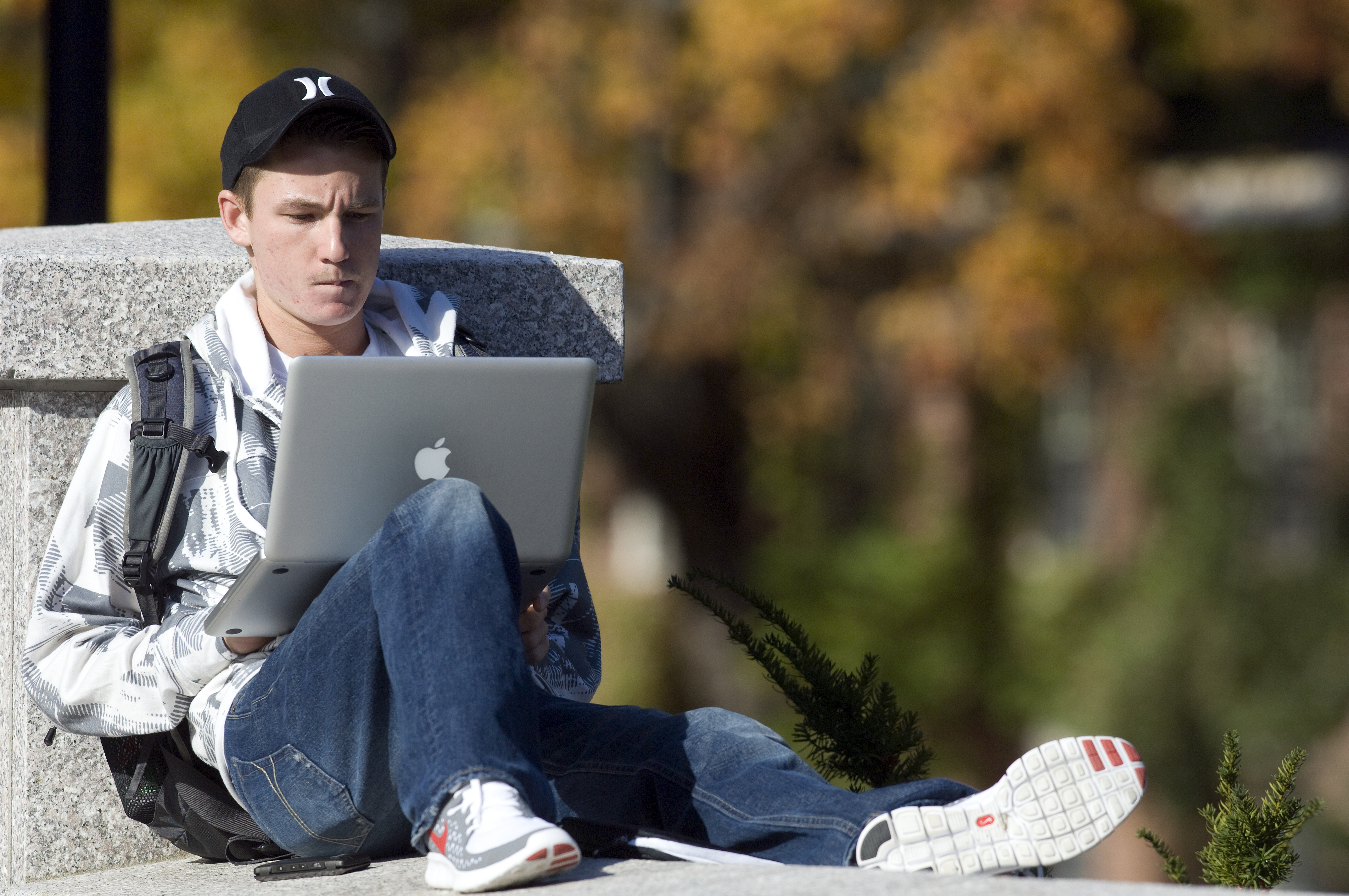 student studying on laptop outside