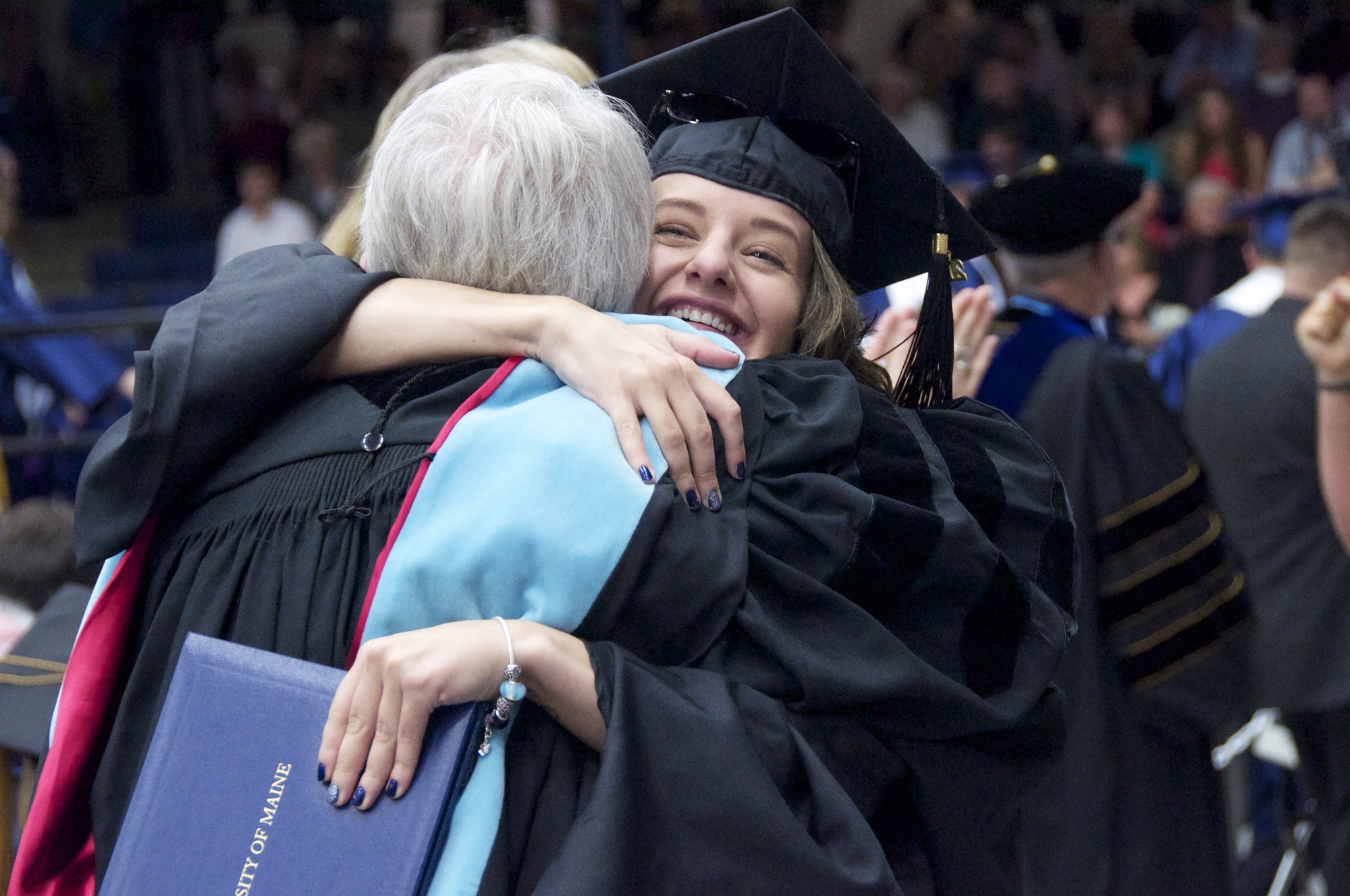 Two students hugging at commencement
