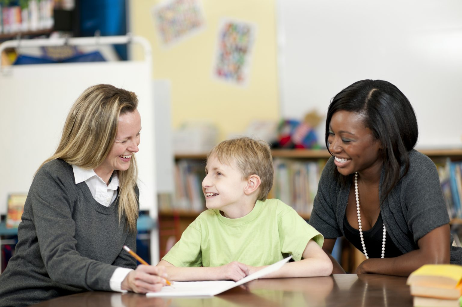 Boy in wheelchair with two teachers at school
