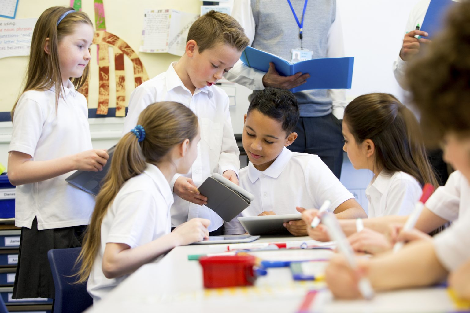 A group of school children can be seen working on digital tablets and whiteboards, they are all working happily. Two unrecognisable teachers can be seen in the background.