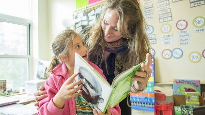 teacher and student looking at book in classroom