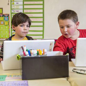 Two male students on a laptop