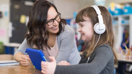 An ethnic first grader teacher sits next one of her students at her desk and checks to see how she's doing. The student is wearing headphones and working on a digital tablet. She has a big smile.
