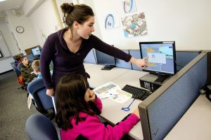 female teacher pointing to computer monitor that a young, female student is working on