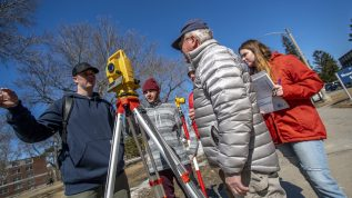 students and instructor outside using surveying equipment