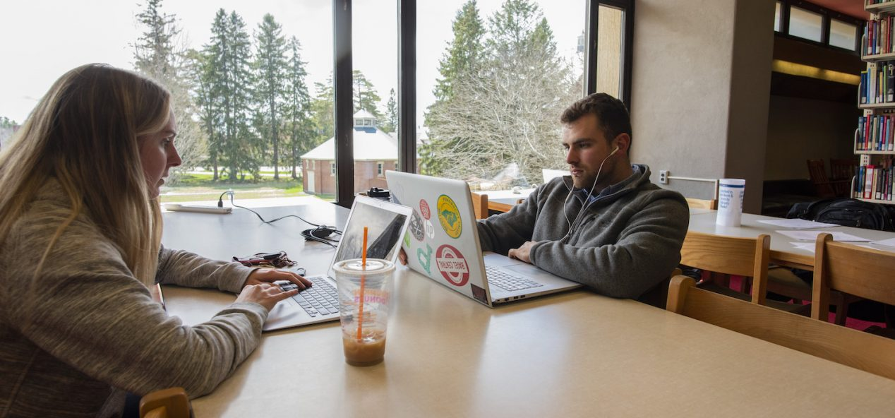 two students working on computers at desk