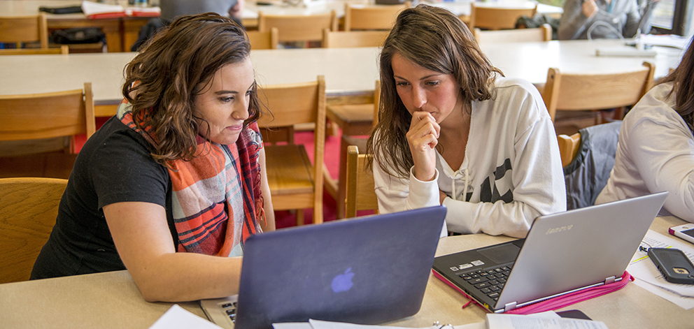 2 students looking at laptop in library