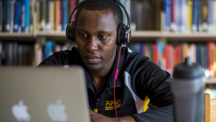 student studying in library with headphones