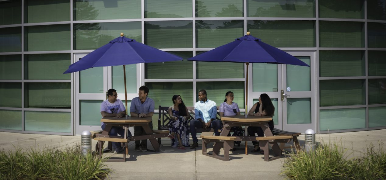 Group of students sitting on benches under umbrellas in front of building