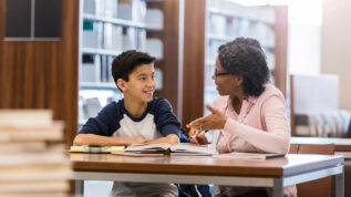 A smiling middle school age boy sits at a table with a mature female tutor in his school library. He listens as she gestures and explains the homework.