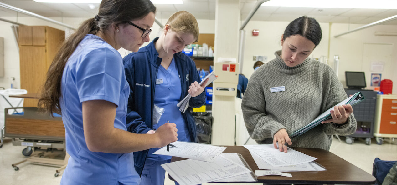 Three female nursing education students examine paper on a table in their lapb
