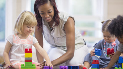 A teacher is sitting on the floor with her preschoolers and day care students - they are playing with plastic blocks together.