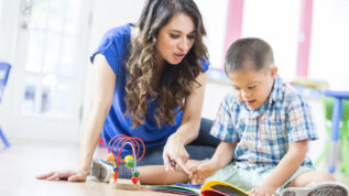 Pretty Hispanic young adult female teacher points at a book and reads to a preschool age Hispanic little boy with Down Syndrome. They are sitting on the floor reading a book together at a daycare center.