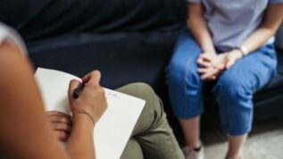 Female psychologist writing notes while meeting with female client