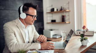 Businessman wearing linen suit and eyeglasses sitting at his desk by the window using laptop and listening music on a headphones