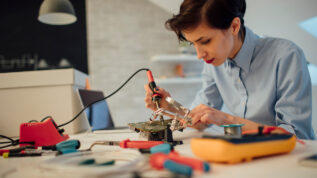 Close up of female engineer using solder in her office. Testing and fixing a circuit board.